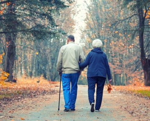 Senior couple walking in an autumn park.