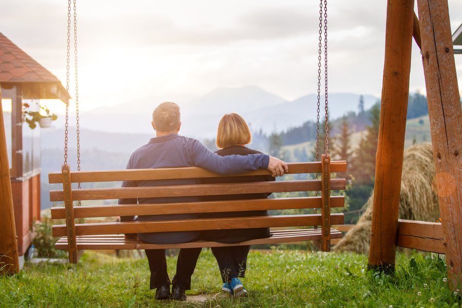 Happy mature couple resting on bench in mountains
