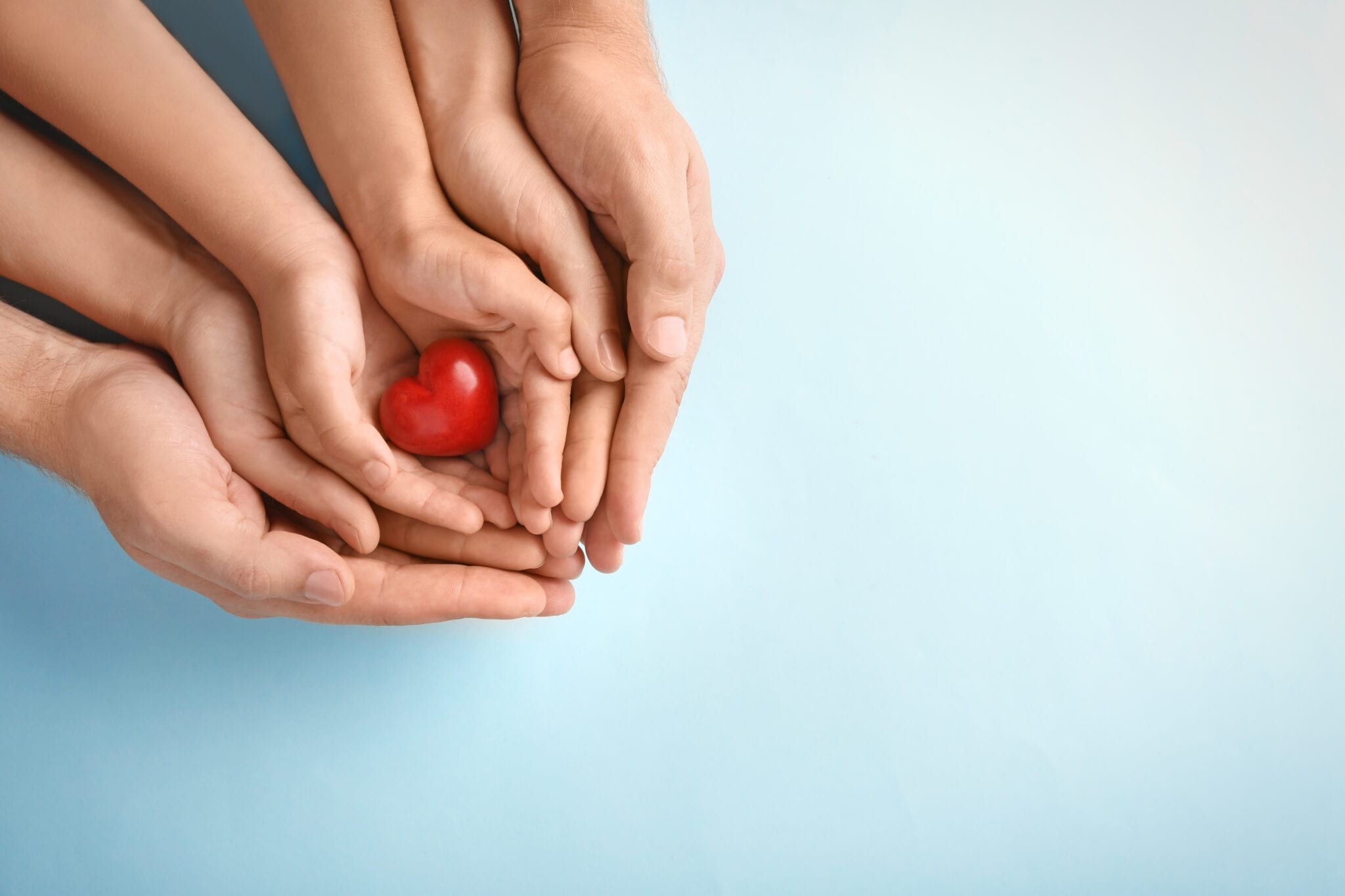 Family holding small red heart in hands on color background