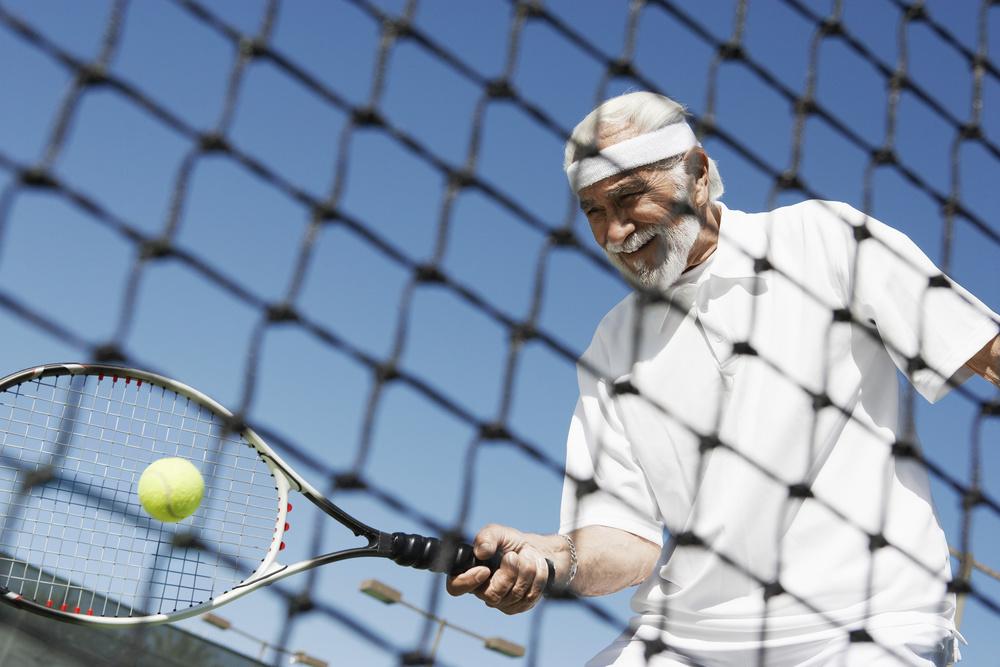 Hombre mayor jugando al tenis.