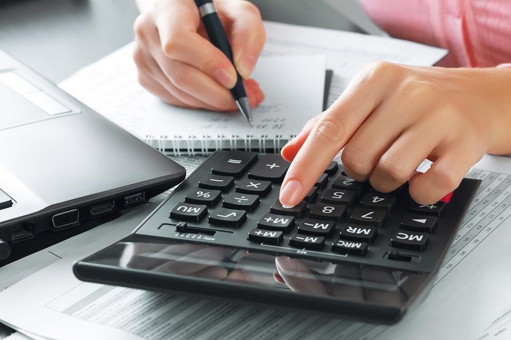Mujer usando una calculadora para hacer la declaración de la renta.